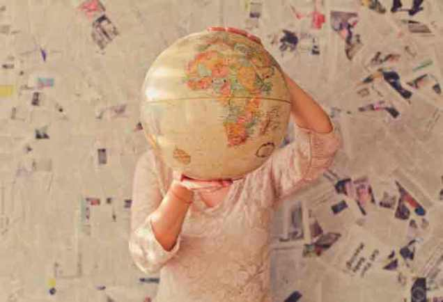 woman holding a globe deciding about remote year travel